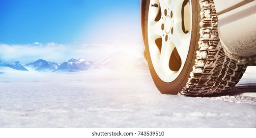 Wheel of a car on a white snowy surface close-up against a background of mountains. Space for text