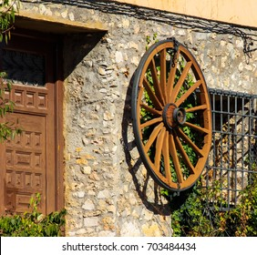 The wheel of the cart on the wall of the house