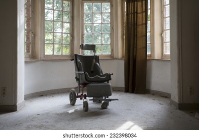 wheel chair by windows in old abandoned hospital