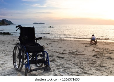 Wheel chair is on the sea beach. The wheelchair owner is a crippled child crawling on the beach. He looked at the boat in the sea.