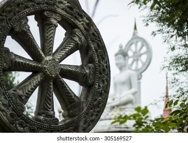 The Wheel of dharma and White budda statue in public temple - thailand