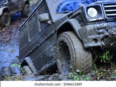 Wheel of dirty offroad car covered with mud, defocused. SUV stuck in dirt with crossover on background. Powerful black car rides with obstacles in forest area. 4x4 racing concept.