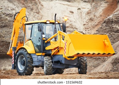 Wheel excavator loader with risen bucket at eathmoving works in construction site or sandpit