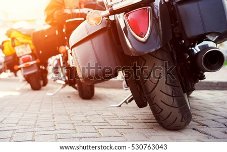 Wheel and exhaust pipe of motorcycle on road. Cropped shot of the motorcycle rear wheel. Motorbike parked on a street. Freedom and travel concept.