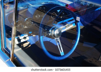 Wheel and fragment retro car dashboard through glass.