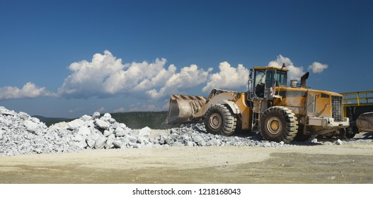 Wheel front-end loader in a quarry on the background of the wreckage of stone and blue sky with clouds, close-up, panorama. Heavy mining equipment.