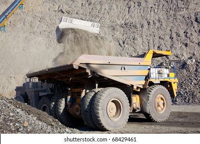 Wheel front-end loader unloading  ore into heavy dump truck at the opencast mining