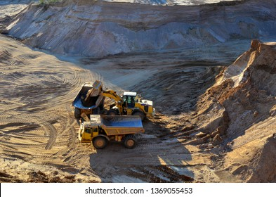 Wheel front-end loader unloading sand into heavy dump truck at the opencast mining quarry