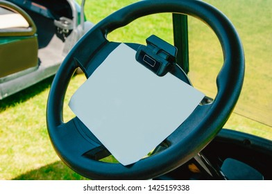The wheel of a golf car with a sheet of paper for records