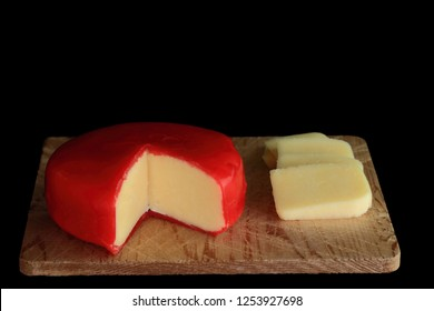 Wheel of Gouda Cheese with cut segment (wedge) and slices wheel of cheese is covered with red wax protective layer on wooden cutting board over black background