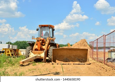 Wheel loader bulldozer with bucket on a construction site. Clearing the ground for digging the foundation pit
