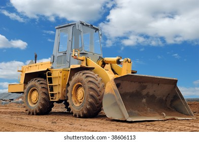 wheel loader bulldozer with bucket standing in sandpit outdoors