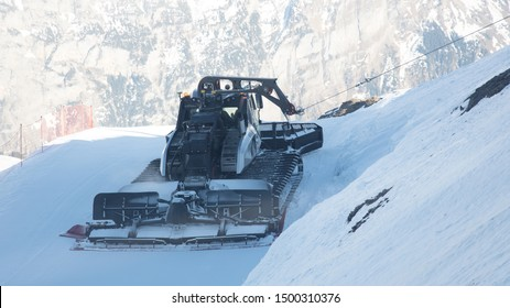 Wheel loader with chains on its tires, for plowing snow at ski resort on the mountain