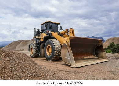 Wheel loader excavator and background of crushed stone hills. Heavy equipment.