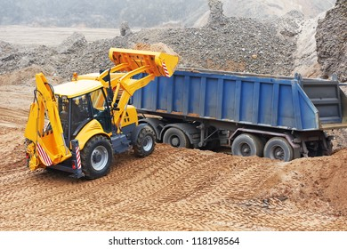 Wheel loader Excavator with backhoe loading sand into dumper truck at eathmoving works in construction site quarry