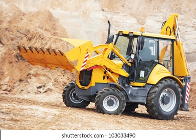 Wheel loader Excavator with backhoe unloading sand at eathmoving works in construction site quarry