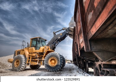 Wheel loader excavator with backhoe unloading clay