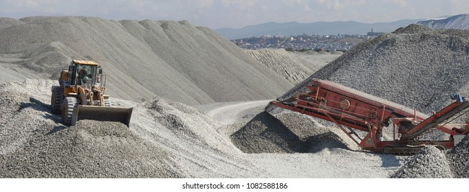 Wheel loader excavator and mobile crusher against the background of crushed stone hills, panorama. Mining industry. Heavy equipment.