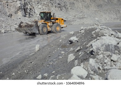 Wheel loader excavator moves along the road in a limestone quarry, close-up. Mining industry. Mine and quarry equipment.