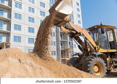Wheel loader Excavator unloading sand on house under construction background