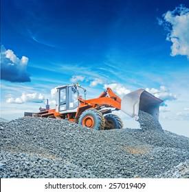wheel loader excavator working with  gravel on big pile