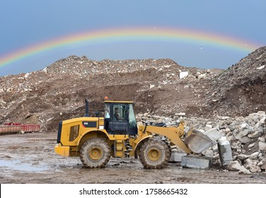 Wheel loader at landfill on rainbow background. Disposal of construction waste and concrete crushing. Recycling concrete and asphalt from demolition. Heavy machinery works in mining quarry.
