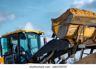A wheel loader loads sand into a silo. Special construction equipment for earthmoving and handling operations.