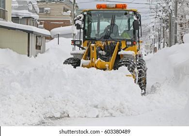Wheel loader machine removing snow in winter