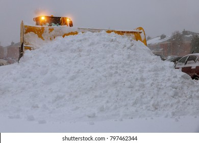 Wheel loader machine tractor removing snow. Clearing the road from ice and snow