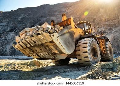 Wheel loader machine unloading rocks in the open-mine of iron ore