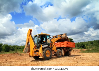 Wheel loader machine unloading soil to the dumper truck  in construction site.