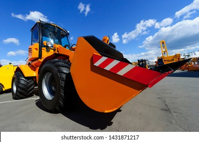 Wheel loader, orange construction machine with big scoop, heavy industry, blue sky and white clouds on background