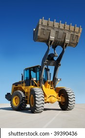 wheel loader over white with fully raised bucket (in focus)