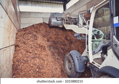 Wheel loader is working with a compost pile as a result of organic wastes recycling process on a biogas plant.