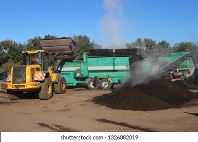 Wheel loader working in a composting facility for biowaste, green waste and sewage sludge. The loader is charging a  screen. The screened compost heap is steaming.