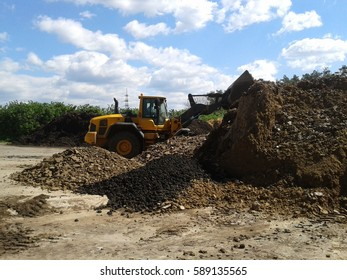 Wheel loader working in a composting facility for dried sewage sludge and green waste