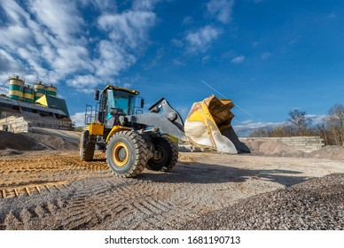 Wheel loader works in a warehouse of sand and gravel. Flyover for unloading railway freight cars. Transportation of inert materials for concrete production.