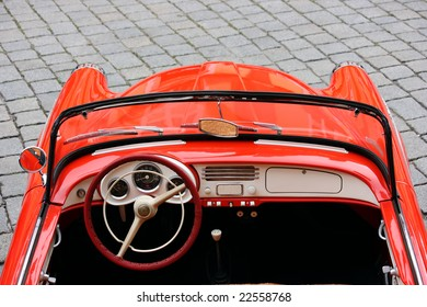 Wheel and part of the interior of a red vintage car