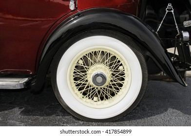 Wheel and partial body of a red antique car.
