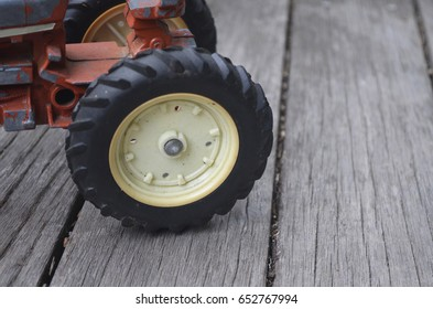 Wheel of red metal antique toy tractor truck