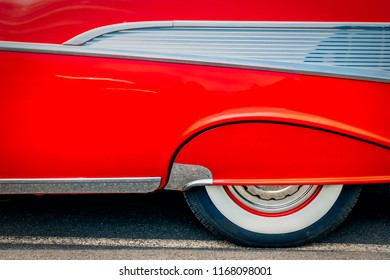 The wheel skirt of a 1950's classic American car in red.