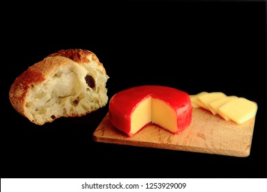 Wheel and slices Gouda Cheese (red wax protective layer covered cheese) cut segment (wedge), over wooden cutting board, broken piece from loaf white rustic country bread on black background