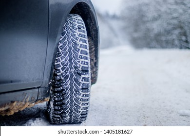 Wheel with spikes on a winter road. Winter road. Snow road. Car on the winter road. Footprints in the snow.