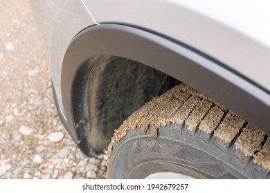 wheel in a swamp under the wing of a suv off road extreme ride, close-up of a tire with a tread and fender of a dirty car.