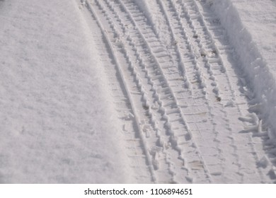 Wheel track on the white snow. Snow road surface of the winter season.