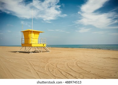 Wheel tracks curving on the sand next to an empty lifeguard post on an empty beach under dramatic blue sky with white clouds