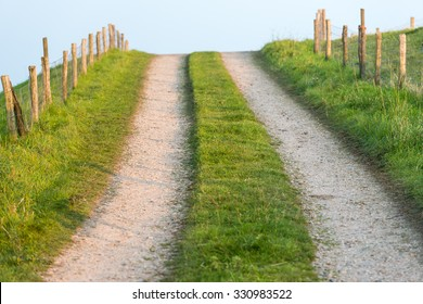 Wheel tracks on a country road up to a dike. On both sides is a fence with mesh and wooden poles. There is low sunlight because it is at the beginning of the evening.
