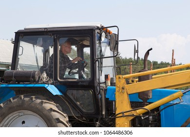 The wheel tractor moves the gravel with a bucket on the construction site. Blue sky and white clouds in the background. Tractor works on a construction site with gravel and sand on a summer sunny day.