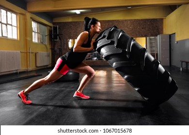 Wheel truck exercises at gym by young strong muscular woman
