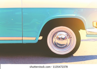 Wheel in a vintage car. Detail of rear quarter panel, whitewall tires and chrome hubcap of vintage car